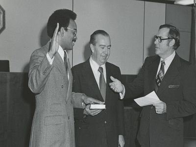 Denson is sworn in by Chair Helsby in 1973. With Member Crowley.